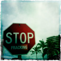 "Stop sign with ""fracking"" sticker under the word Stop."